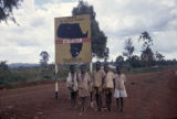 Kenya, group of boys posed under sign at equator between Kisumu and Kakamega
