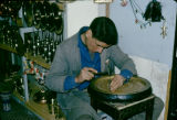 Tunisia, artisan making designs on brass tray