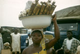 Ghana, woman carrying bowl of sugar cane on head