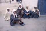 Tunisia, men sitting along building