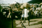 Ghana, men unloading bags of cocoa from truck in Accra
