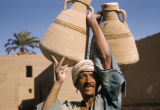 Egypt, man carrying water jugs