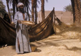 Egypt, man sifting wheat in the farm village