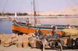 Egypt, man on a freshly painted boat on the shore of the Nile River