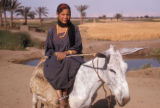 Egypt, portrait of a Bedouin girl riding a donkey