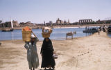 Egypt, people carrying baskets on the shore and Temple of Luxor in background