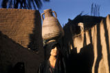 Egypt, woman carrying water jug on her head