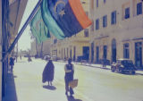 Libya, pedestrians walking on sidewalk beneath flags in Tripoli