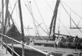 Egypt, men on wooden ship on Nile River with sailboats in background