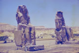 Egypt, man standing at base of Colossi of Memnon near Thebes