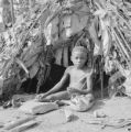 Democratic Republic of the Congo, Mbuti boy in front of hut holding bow and arrows