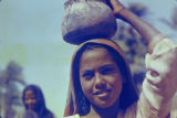 Egypt, portrait of girl carrying stone jar on head
