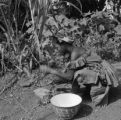 Liberia, woman using rock to crush seed pods