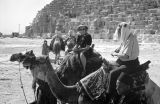 Egypt, Western man and woman on camels in front of Giza pyramid