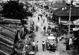 Nigeria, pedestrians and cars on side street in Lagos