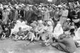 Morocco, people sitting along road watching royal review of troops in Fez