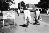 Nigeria, men riding bicycles in Kano past 'No Waiting' sign