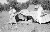 Morocco, Berber woman and child at tent in camp