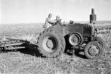 Morocco, men riding tractor at farm near Middle Atlas mountains