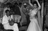 Egypt, woman belly dancing for Western tourists inside tent in Cairo