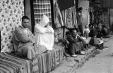 Morocco, people sitting along street in Jewish Quarter of Marrakech