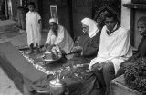 Morocco, men sitting around tea tray on city sidewalk