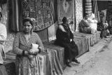Morocco, people sitting on rug covered benches in Jewish Quarter of Marrakech