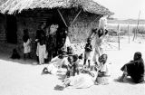 Cameroon, Bantu family gathered outside mud hut