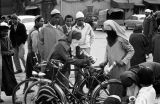 Morocco, veiled women placing items in bicycle bag at Jamaa el-Fna Square in Marrakech