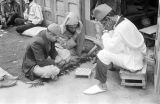 Morocco, men playing checkers on sidewalk in front of shop