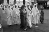 Morocco, women in niqabs and abayas walking in street