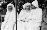 Morocco, robed men sitting in grandstand at royal review of troops in Fez