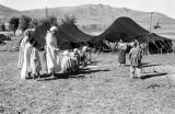 Morocco, Berbers gathered outside of tents at camp in Atlas Mountains