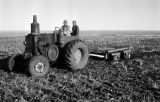Morocco, men riding tractor in farm field near Middle Atlas mountains