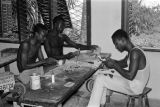 Benin, men carving wood sculptures at workshop