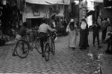 Morocco, boys walking bicycles through souk