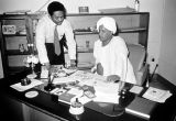 Nigeria, businessmen in discussion at desk in Kano office