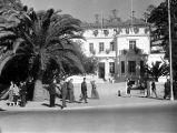 Morocco, pedestrians walking past building adorned with Morocco flags in Rabat