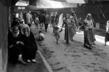 Morocco, people walking under banners through souk