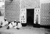 Nigeria, men outside Kano home decorated with geometric and animal designs
