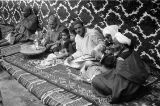 Morocco, men and boys seated on rugs in Marrakech souk