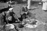 Morocco, Berber men cooking over fire at camp in Atlas Mountains
