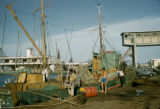 Senegal, men loading fishing boat in harbor