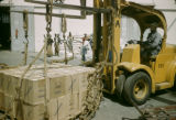 Senegal, man lifting boxes with machinery