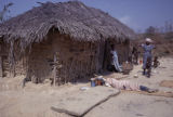Senegal, people outside of square-shaped house with mud walls