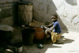 Senegal, child doing laundry in buckets