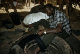 Burkina Faso, man stripping rubber tires for reuse