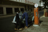 Dakar, man pumping gas into car on street in Senegal