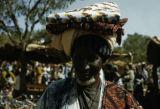Burkina Faso, man carrying textiles on head