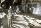 Senegal, woman, child, and goat in courtyard on Gorée Island